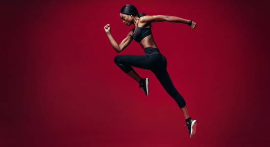 Sports woman running over red background
