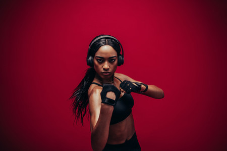 Young woman in sportswear boxing on red background