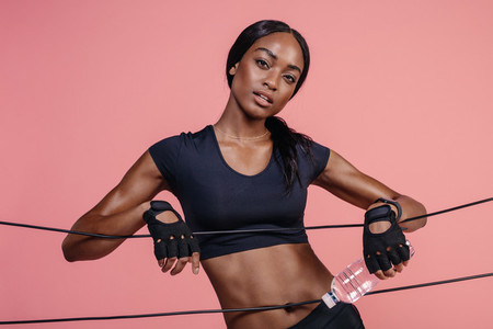 Muscular woman with rubber bands in studio