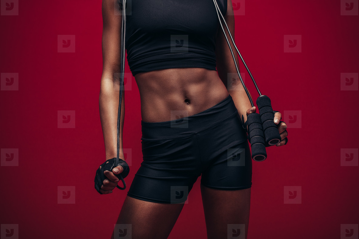 Woman with muscular abs holding jumping rope