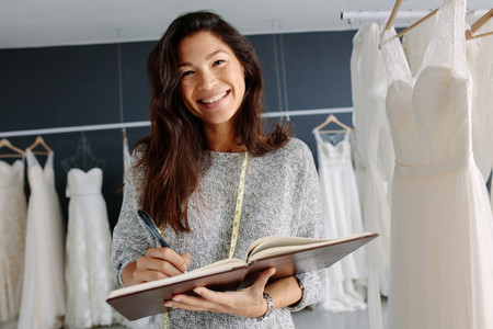 Asian woman tailor working in bridal boutique