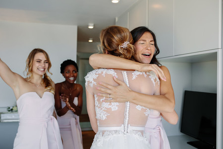 Bridesmaid congratulating the bride before wedding ceremony