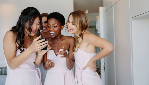Bridesmaids using mobile phone on the wedding day