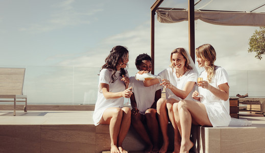 Bride and bridesmaids having a bachelorette party on rooftop