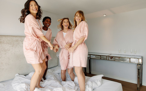 Bride and bridesmaids jumping on bed before wedding