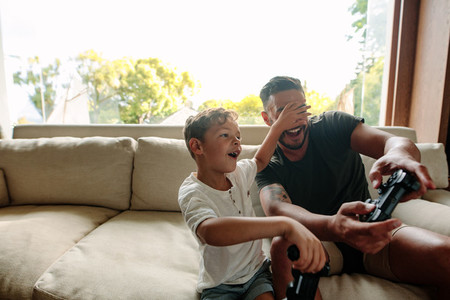 Cheerful father and son enjoying playing video game