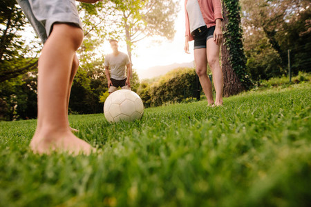 Family playing football in garden lawn