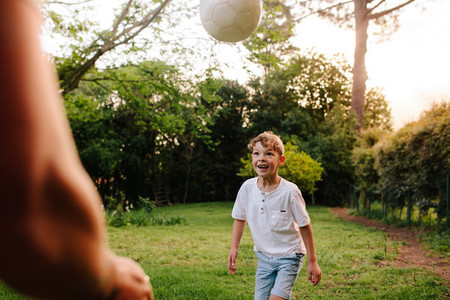 Cute little boy playing football with his father