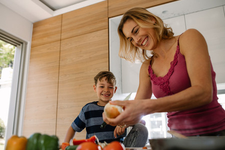 Happy mother and son preparing food in kitchen