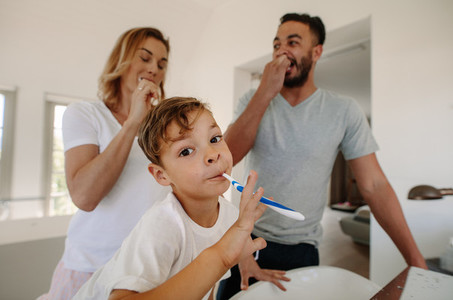 Little boy brushing teeth with his parents