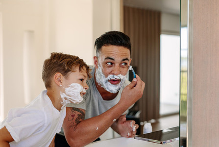 Father and son shaving together in bathroom