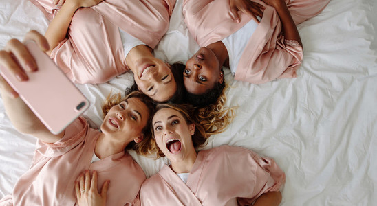Bride taking selfie with bridesmaids making funny faces