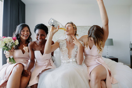 Bride and bridesmaids enjoying before wedding in hotel room
