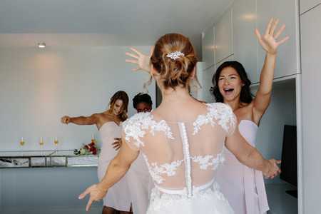 Bride and bridesmaids having fun in hotel room on wedding day