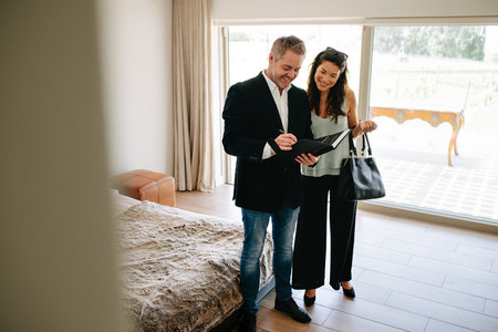 Property adviser showing terms of contract to female buyer