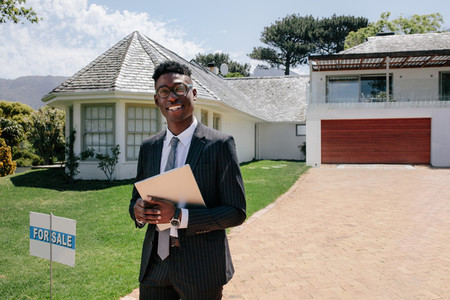 Real estate agent standing outside a house for sale