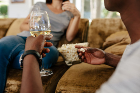 Couple at home drinking wine and eating popcorn