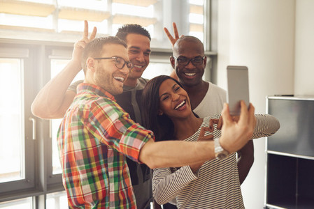 Smiling office workers taking selfie with horns