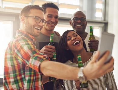 Office team taking selfie with beer bottles