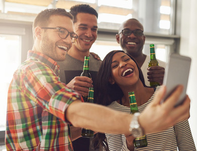 Office team taking selfie with beer bottles