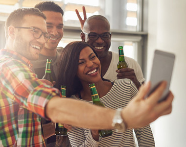 Cheerful team taking theselfie with beer