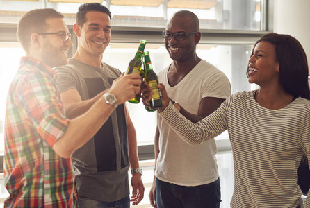 Cheerful people clanging beer bottles in office