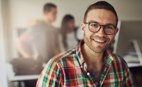 Cheerful entrepreneur wearing glasses in the office