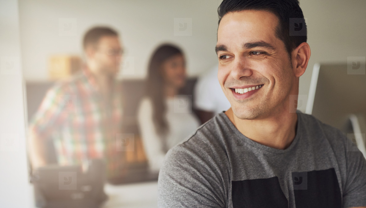 Smiling contemporary businessman looking away in office