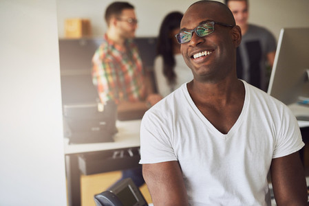 Cheerful confident black businessman sitting in office