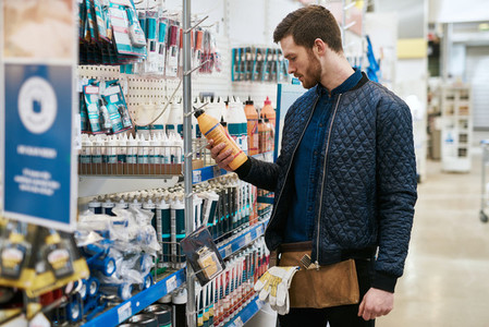 Handyman selecting a product at a hardware store