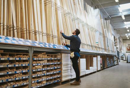 Young handyman selecting a length of cut timber