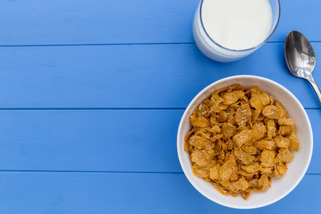 Cornflakes breakfast cereal bowl with milk on wood table backgro