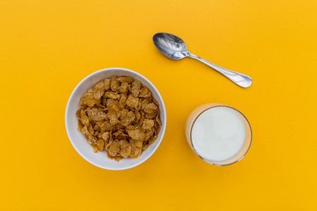Breakfast cornflakes cereal with milk on yellow background