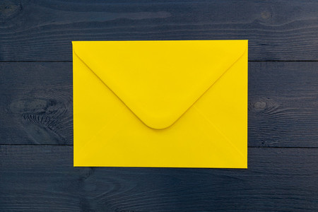 Bright yellow envelope on blue wood table