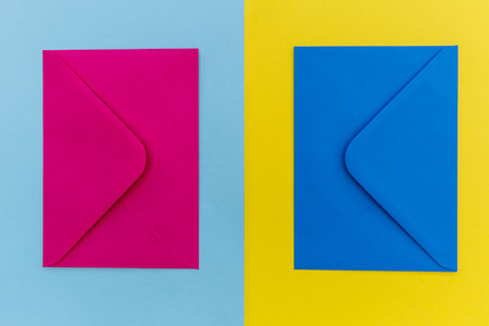 Colorful pink and blue envelopes on yellow background