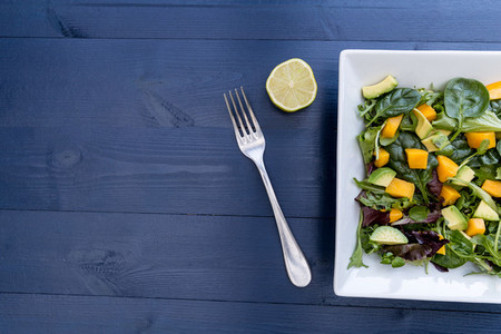 Healthy mango avocado salad with fork lime and copy space