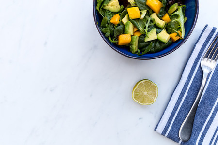 Healthy bowl of mango avocado salad and fork on white marble bac