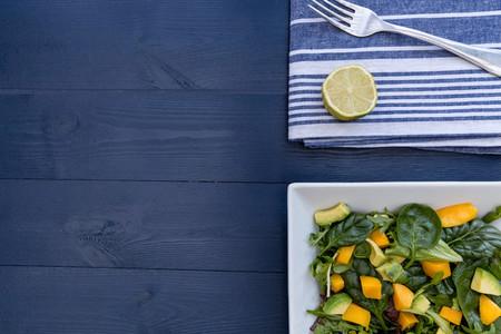 Mango avocado salad on table with copy space