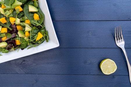 Lunch plate of mango avocado salad on blue wood table