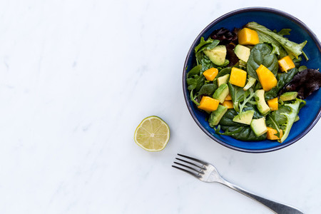 Bowl of mango avocado salad on white marble background
