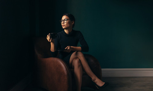 Businesswoman sitting on chair and having coffee