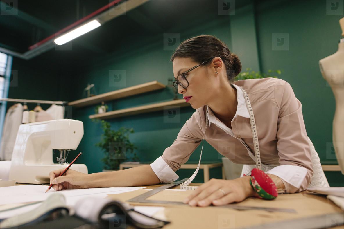 Fashion designer preparing design drafts on paper