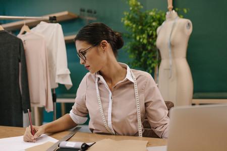 Fashion designer sketching new dress designs