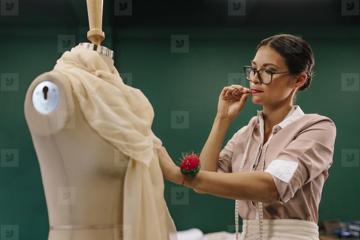 Female designer working on mannequin