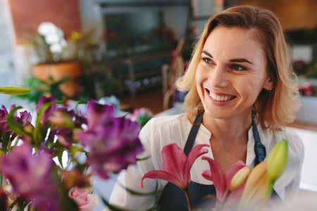 Happy female florist at flower shop