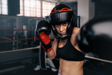 Female boxer in action inside the boxing ring