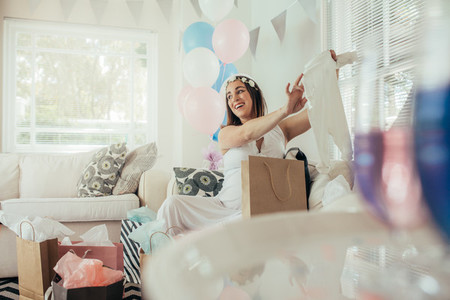 Pregnant woman with new gift at baby shower