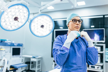 Female surgeon with surgical mask at operating room