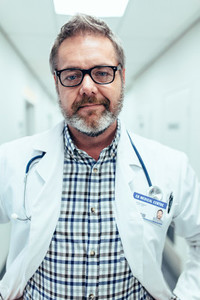 Portrait of mature doctor standing in hospital