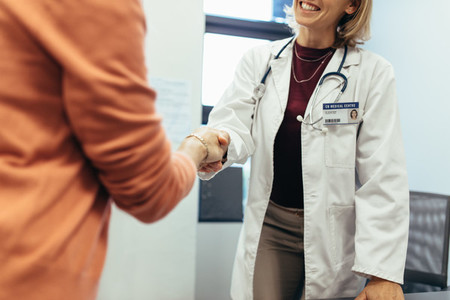 Friendly doctor shaking hands with patient